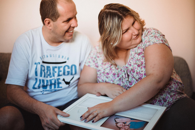 Henriqueta e Cristiano, sentido a foto deles em alto relevo - Foto: Nataly Motta