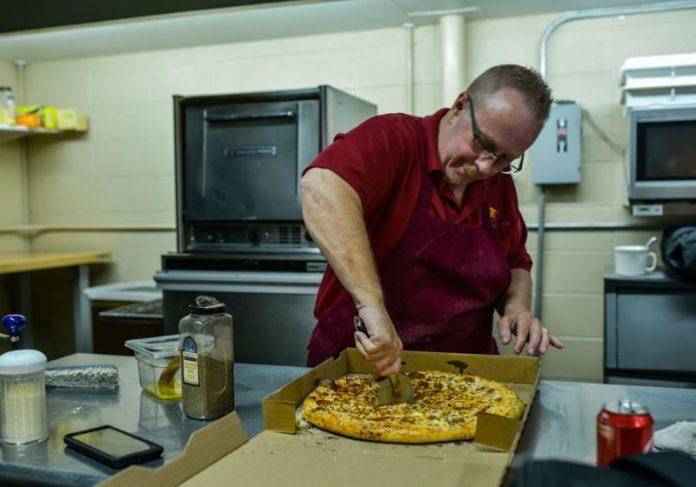 Jeff Minton corta um pedaço de pizza enquanto trabalha na 8th Street Pizza Foto: Tyler Stewart