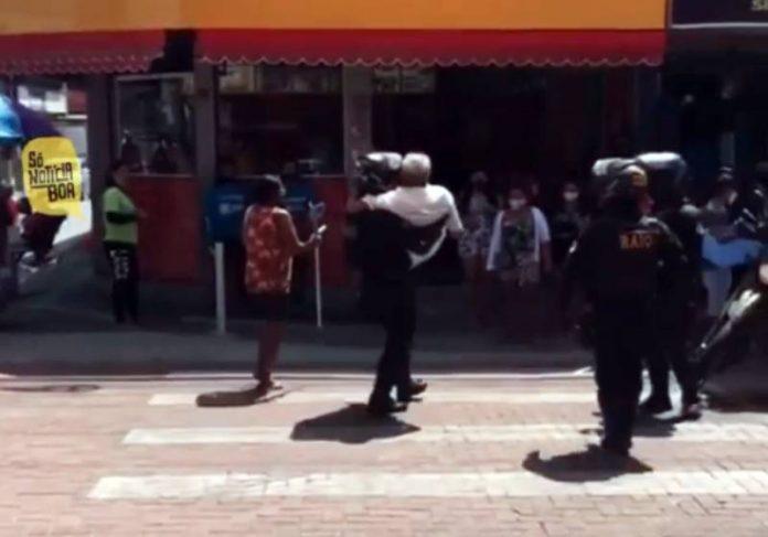O PM atravessando com o idoso nos braços no CE - Foto: reprodução / Instagram