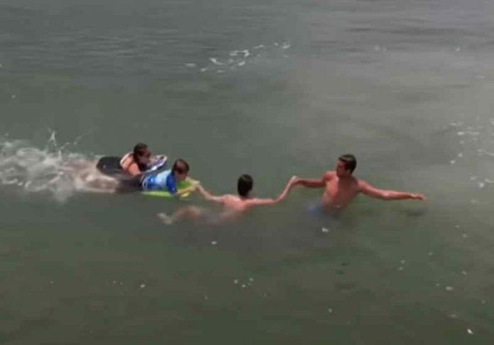 Após salvar mãe e filho do afogamento, o adolescente recebe ajuda de um banhista Foto: reprodução YouTube