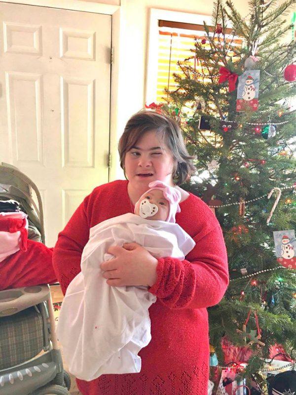 Jovem Down com sua boneca - Foto: reprodução / Facebook