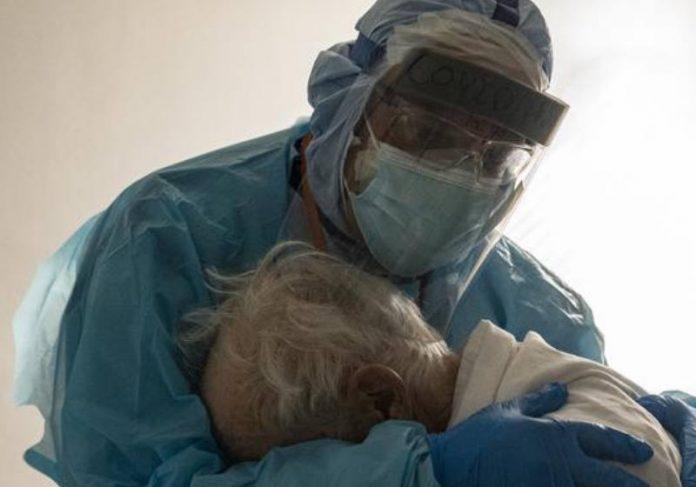 O Dr. Joseph Varon conforta um paciente idoso na UTI Foto: Go Nakamura / Getty Images