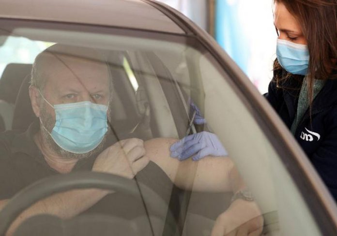 Homem é vacinado em drive-through de Haifa, Israel - Foto: Ammar Awad/Reuters