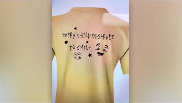 """Camisetas de Peyton que arrecadam dinheiro para sua instituição. Está escrito """" Toda criança merece sorrir"""". - Foto: L. Anderson"""
