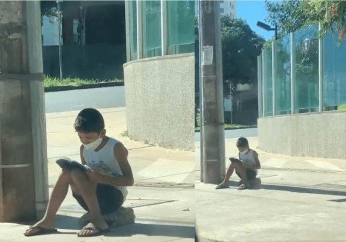 Nícolas lendo a Bíblia na calçada - Foto: reprodução / Instagram