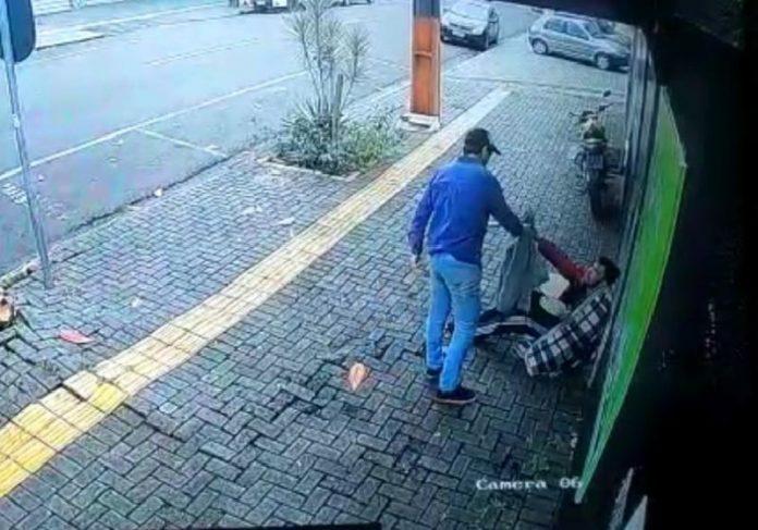 O vendedor ambulante Gabriel doando a própria blusa à pessoa em situação de rua - Foto: câmeras de segurança / G1