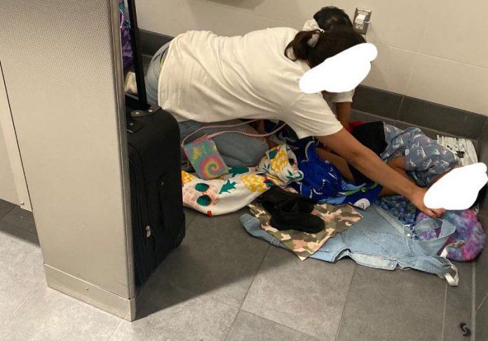 Mulher dormia no chão do aeroporto com o filho pequeno. - Foto: reprodução Cyn Simoné