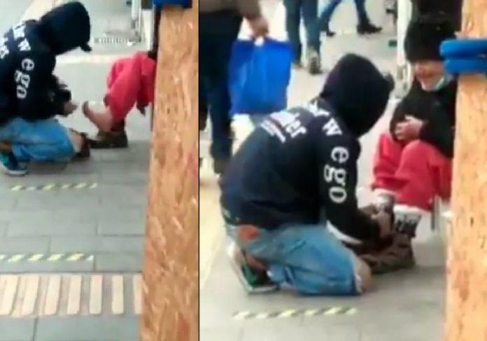 O rapaz vestiu a meia na idosa com frio e depois deu dinheiro a ela - Fotos: reprodução / Twitter