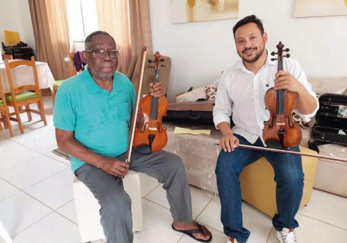 Nerlson e o professor de violino, Giovanny Conte. O aposentado sempre sonhou em tocar um instrumento. — Foto: Karla Mendes